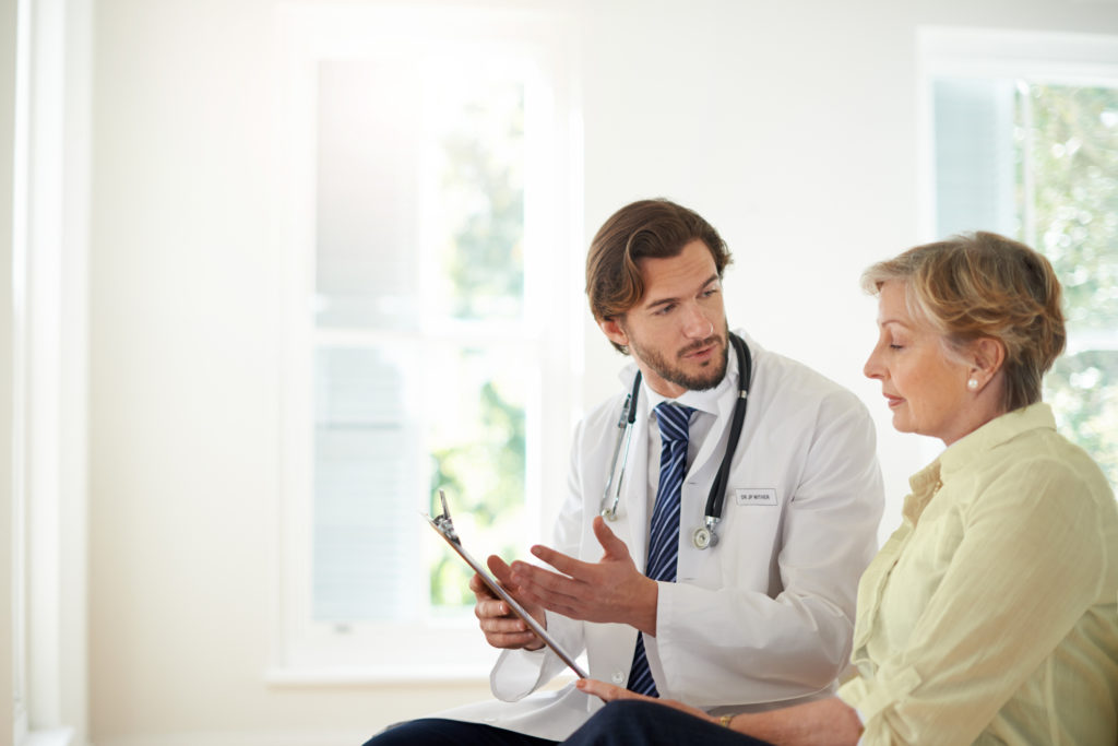 Cropped shot of a doctor talking to a senior patient in a clinic