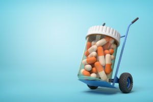 3d rendering of a plastic jar with medical pills on a hand truck on blue background. Medicine and health. Bottles and containers. Healthcare industry.