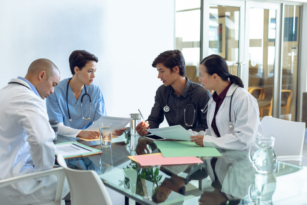 Medical team discussing with each other at the table in hospital