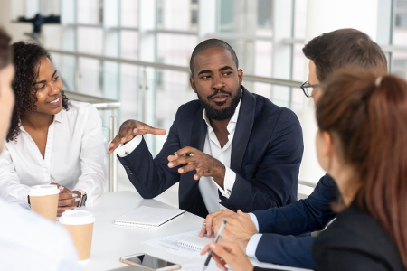 Millennial employees gathered in boardroom for training, black boss ceo leader leading corporate team during seminar learning at modern office. Internship and leadership coaching and education concept (Millennial employees gathered in boardroom for tr