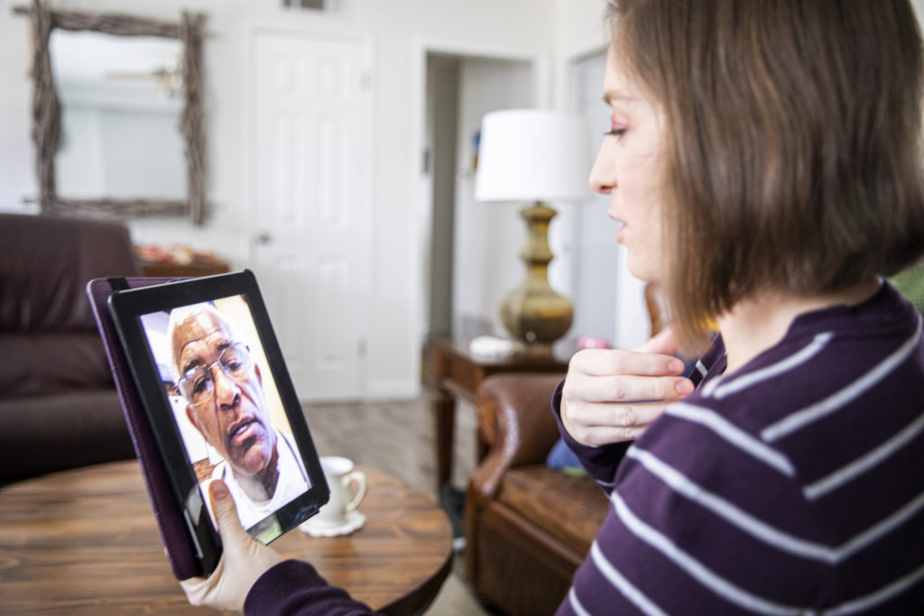 A young woman receiving healthcare through video call
