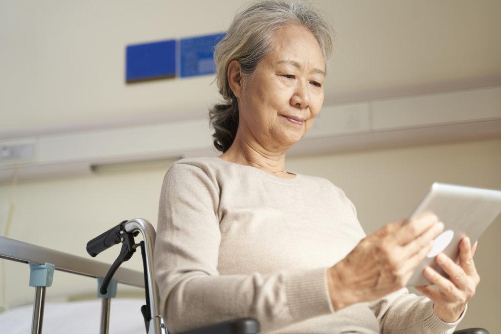 asian senior woman using digital tablet in nursing home or hospital ward